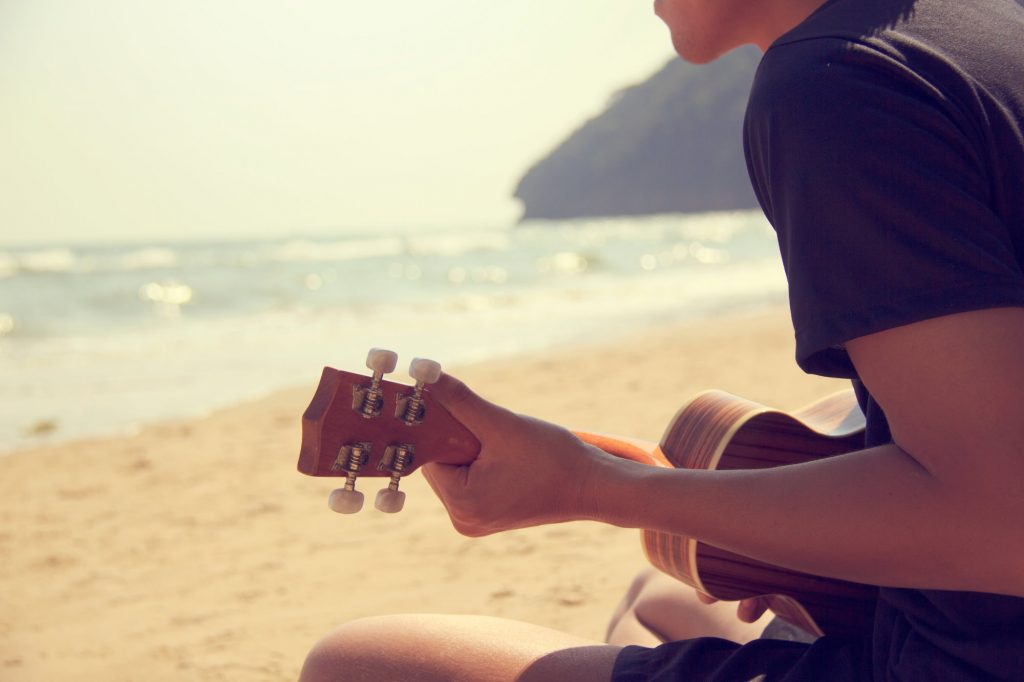 Man playing ukulele on the beach